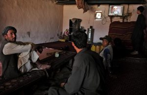Afghan customers at a tea house in Kabul watch the breaking news