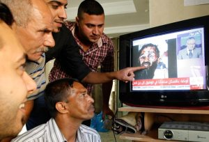 Iraqis in Baghdad watch a news broadcast on Arabic satellite news channel Al-Arabiya